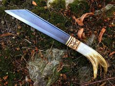 """A simple yet aggressively straightforward """"broken back"""" seax. Forged from 1075 high carbon steel, antiqued and engraved with the owners name-rune. The grip crafted from brass, stag antler, and maple wood with """"maze & key"""" geometric designs."""