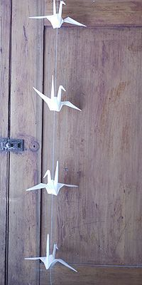 Origami crane garlands...diy on how to string them with tips on where to string though their bodies so they're strait and don't move.