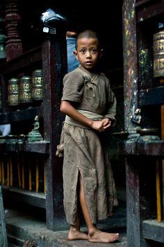 Nepal by Richard Lewisohn --- 7-year-old monk 'on duty' outside the Golden Temple in Patan, Nepal
