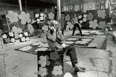 Warhol in the Factory surrounded by Flowers prints. His assistants goof off in the background.