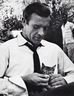 """Sean Connery playing with a kitten on the set of """"Dr. No,"""" 1962."""