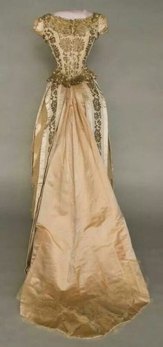 Rear view 1880-1885 gold brocade ball gown.