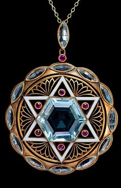 Art Deco Star of David Aquamarine Pendant.  An original pre World War II Art Deco pendant designed as a round openwork matte gold plaque with a white enamel six pointed Star of David set with a hexagonal aquamarine and six small rubies. The star is flanked by six Art Deco openwork floral ornaments encircled by twelve navette cut aquamarines, ca. 1930.