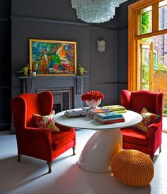 Dark neutral room with punchy accents: Orange French doors, red armchairs, and glossy white table