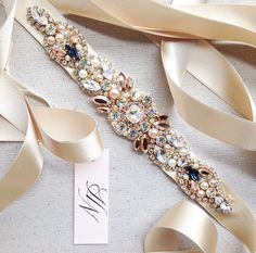 A classic statement, this lovely sash is meticulously hand-beaded with gorgeous Swarovski crystals, sequins and pearls. Delicate ivory ribbon is attached for a bow closure. -Available in any color combination {shown here in rose gold, pink champagne, gold and ivory….and a touch of navy blue}. -Beaded part measures approximately 8″ in length. This can be …