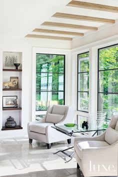 Love the contrast between the white chairs, black trim on large windows and the wonderful green view