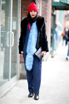 winter outfit - navy blue jumpsuit, pastel blue stole, bright red beanie with veil + black fur winter coat
