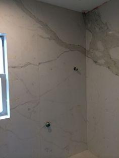 Calcutta gold porcelain slab shower wall by Casalinea US in Houston.
