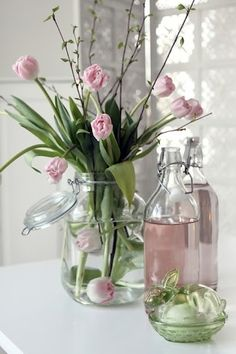soft pink tulips in a glass jar of a vase with rose pink water in glass bottles and a small green glass