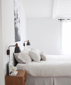 White bedroom with black and gold sconces and black and white art over bed.