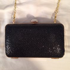 Black evening clutch This elegant evening clutch has never been used before and is it perfect condition. The outside is black and shimmery with a silver rhinestone clasp and gold trim. The gold metal strap inside can be used to wear this cross body or over the shoulder. Simple and elegant. Bags Clutches & Wristlets
