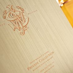 The box was crafted using complex rigid board construction, and is wrapped in bespoke paper stock, debossed with a fine wood grain effect. On the front of the case, the John Walker & Sons monogram is displayed in deep copper foil. Providing a striking contrast is the silver foil Royal Warrant emblem. The whisky bottle is held snugly in a fitted recess in the main body of the case, and can be easily slipped out with an attached copper ribbon. Opposite rests a hardback information booklet. John Walker, Luxury Packaging, Wood Grain, Booklet, Whisky, Bespoke, Sons, Contrast, Ribbon