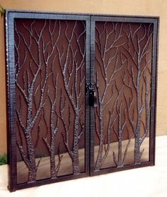 Hand forged built-in fireplace screen with customized tree motif and hand forged latch closure.
