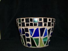 Terracotta pot mosaicked in green and blue with recycled glass and found objects.