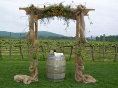 Wedding arch idea but add some blue and use wine barrel as table for candles or sand jars