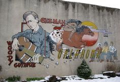 Mural at 510 West Broadway, Hwy. 56, downtown Okemah, Oklahoma, depicting Woody Guthrie and Okfuskee County history. Painted by DeAnna Wilson in 1994.