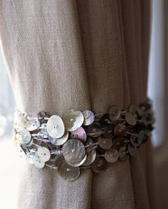 Mother Of Pearl Curtain Tie Back. Multi layered strands of buttons and clear crystal beads. Black lacquered mother of pearl buttons and jet crystal detailing: http://spinadesign.co.uk/media/catalog/product/cache/1/image/9df78eab33525d08d6e5fb8d27136e95/i/m/img_8099.jpg