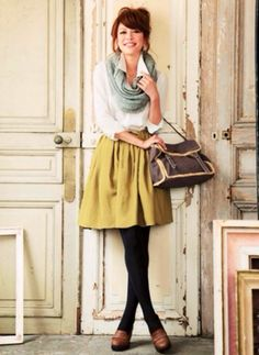 Girl wearing a short mustard yellow color skirt  with a white collar button down shirt & scarf with black leggings
