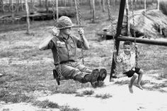 A young Vietnamese child and a U.S. soldier of the 25th infantry division test a swingset in a new playground at the American base in Cu Chi, Vietnam. The playground, part of an improvement project, was built by members of the 25th.