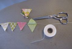 This week I crafted a mini pennant flag garland for a client's nursery.  I made it using scraps of fabric, nylon thread, pinking shears, fus...