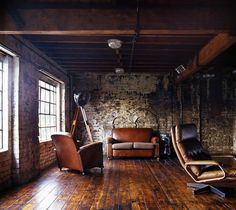 distressed brick, weathered and oiled hardwood floors; exposed beam celing, and lots of aged leather furniture..