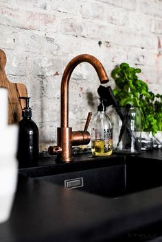Exposed brick, brass taps and black marble