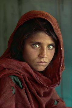 """""""Afghan Girl"""" - Although her name was not known, her picture, titled """"Afghan Girl"""", appeared on the June 1985 cover of National Geographic. The image of her face, with a red scarf draped loosely over her head and with her piercing sea-green eyes staring directly into the camera, became a symbol both of the 1980′s Afghan conflict and of the refugee situation worldwide. The image itself was named """"the most recognized photograph"""" in the history of the magazine."""