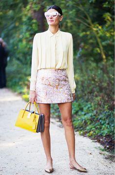 Giovanna Battaglia in a brocade mini skirt, feminine blouse, bright handbag, oversized sunglasses, and metallic flats