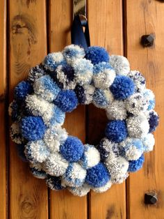 A beautiful hand-crafted pom-pom wreath, to adorn any door in your home. The wreath measures approximately 10.5 inches in diameter wrapped in lovely cotton printed fabric, adorned with 44 fluffy blue poms each individually made by me. The wreath hangs on a dark navy ribbon. This is the only wreath in stock. Similar wreaths can be made upon request to suit your personal preferences, so please get in touch and I will be happy to help