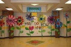 """What do you love about art?""  Large paper flowers with petals created from painted papers by students.  Each students creates a leaf with a comment about why they love art to go on the stems."