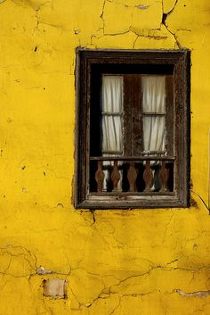 window with broken yellow wall