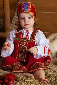 A cute blue-eyed girl is wearing Russian traditional costume.