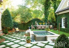 A verdant, perfectly manicured Brookhaven backyard by features Mondo grass-accented lattice stonework, a luxurious…