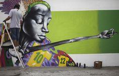 Seniman grafiti Barba bekerja pada mural dalam rangka perayaan kejuaraan sepak bola Piala Dunia 2014 di Rio de Janeiro, Brasil. Mural itu akan menjadi bagian dari sebuah kontes yang diselenggarakan oleh balai kota di kota itu.