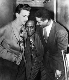 Charlie Parker with Dean Benedetti (left) and Max Roach (right), leaving The Three Deuces New York, 1948