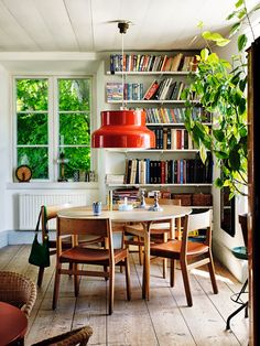 Wonderful bookshelf in a very green apartment with big red lamp above the wooden table