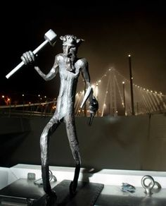 In this Monday, Sept. 2, 2013 photo provided by the Bay Area Toll Authority, a bridge troll stands by the Bay Bridge's east span tower shortly before the bridge opened to traffic in San Francisco. The final piece of safety hardware — a bearded, spindly legged troll — has been installed in the new eastern span of the San Francisco-Oakland Bay Bridge. The troll is meant to be a protector and good luck charm, modeled after a similar statue placed surreptitiously by a steelworker on the old span…