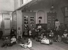 Kleutertehuis in Schiedam. In een klaslokaal zitten kleuters op de grond te spelen met poppenwiegjes of hobbelpaarden. Andere kinderen zitten aan tafeltjes. De kinderen kijken allemaal naar de fotograaf. Achter in de klas twee kleuterjuffen. Schiedam, Nederland, 1921.