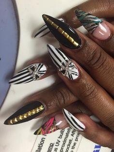 festive nail art, black and white stripe nail art, gold nail designs, stiletto shape nails, rhinestone nail designs, long nails, exotic nail art, bright nails, zebra print nail designs, fun nail art tips, stripe nails