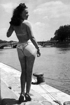 """On July 5, 1946, French designer Louis Reard unveils a daring two-piece swimsuit at the Piscine Molitor, a popular swimming pool in Paris. 19-year-old Parisian showgirl Micheline Bernardini modeled the new fashion, which Reard dubbed """"bikini,"""" inspired by a news-making U.S. atomic test that took place off the Bikini Atoll in the Pacific Ocean earlier that week."""