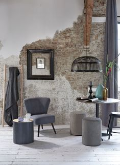 Industrial room with grey armchair, ottoman, metal stool and wooden side table…