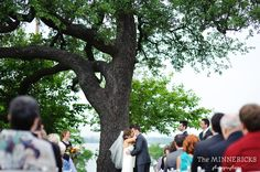 First kiss under a tree, with a lake as a background, at Amanda and Brian's outdoor, Summer wedding at Winfrey Point on White Rock Lake. Expertly crafted, vividly emotional, wedding photojournalism by The Minnericks Photographers. Dallas, Texas.