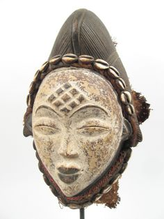 Punu mask with cowrie shell decoration via Gotham Gallery of African Art
