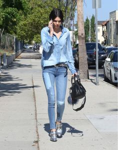 Kendall Jenner wears a button-down denim shirt, patchwork jeans, and silver oxfords