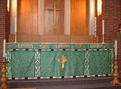 """St. Andrews Altar 3:  Anglican church altar set up for """"ordinary time"""", with green altar cloth with gold crosses and """"Sanctus Sanctus Sanctus"""" (""""Holy Holy Holy"""") embroidered on it.  Wood and brass candlesticks, wood and brick walls, and white candles complete the picture.  Image size 1725 x 1275px (300ppi).  Prints at 5.75 x 4.25""""."""