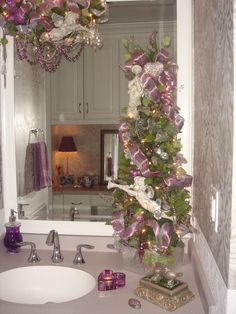 Shabby chic purple bathroom decorated for Christmas with cherubs and a garland with beads and lights hanging from the mirror