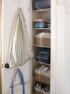 A+pair+of+narrow+closets+provides+ample+storage+for+clothing+and+shoes.+Baskets+corral+socks+and+shoes,+while+hooks+for+laundry+and+tote+bags+maximize+back-of-the-door+space.