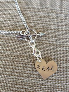 'You love me, real or not real?' 'Real'.  Hunger games inspired arrow with a hand stamped heart saying 'real'.