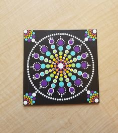 This 6x6 dotilism mandala painting features a rainbow burst design with careful white borders to simultaneously draw the eye inward to the center and outward toward to the border. ------- Medium: Acrylic paint on canvas panel with varnish finish ------- Options: For $2 extra, add