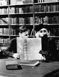 Clark Gable and Marion Davies at the library reading large book in a scene from the film 'Cain And Mabel', 1936.